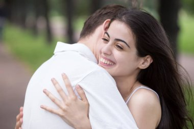 Young attractive couple in love embracing outdoors