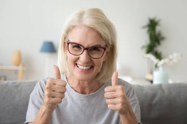 Excited elderly woman show thumbs up recommending something