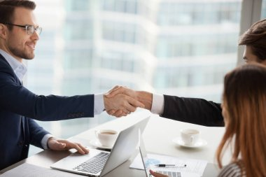 Young businessman handshaking business partner after successful negotiations. Deal with good result, start of work with business partner, conclusion of an agreement, good relationships, human