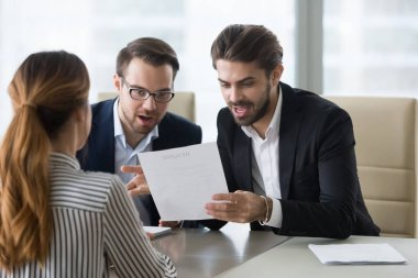 Surprised funny human resources managers reading resume of best applicant ever. Suitable candidate for vacancy. Smiling recruiter, employer. Successful job interview, hiring, staff recruiting process.