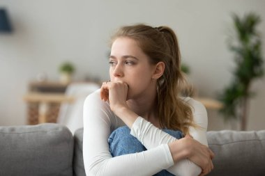 Sad woman sitting on couch alone at home