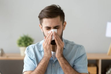 Young sick man holding handkerchief sneezing at work