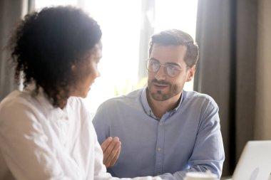 Friendly male mentor explaining african american female intern n