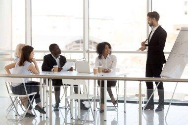 Millennial male mentor make flipchart presentation to colleagues