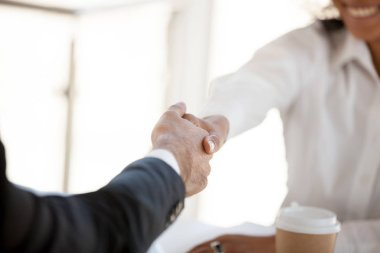 Close up of diverse colleagues handshake greeting at meeting