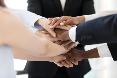 Diverse employees stack hands in pile showing support and unity