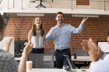 Excited team leader congratulating employee with promotion while