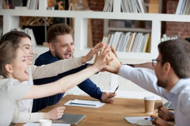 Excited employees give high five celebrating shared success