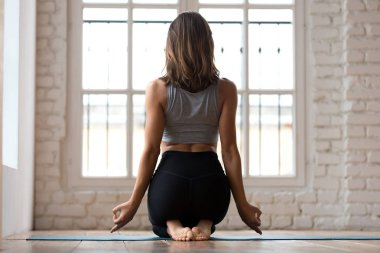Young woman practicing yoga, doing exercise in sitting pose