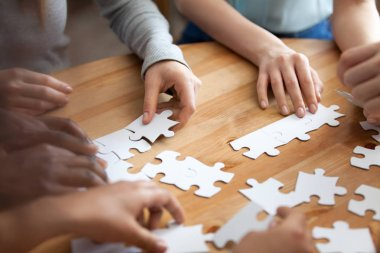 Hands of multiracial people assembling puzzle close up