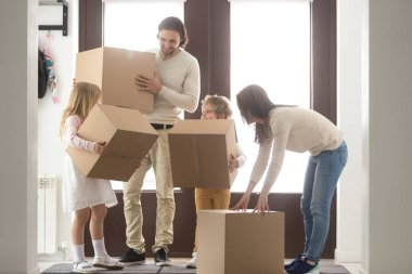 Young family with cardboard boxes at new home