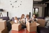 Famiglia felice con scatole di cartone nella loro nuova casa