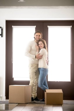 Couple standing with unopened cardboard boxes looking at camera