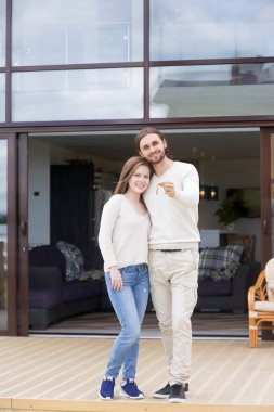 Couple in love standing on terrace of new house