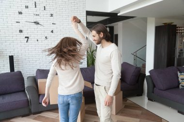 Married excited young couple dancing together in sitting room