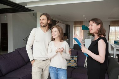 Realtor showing property for sale to young married couple