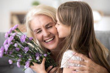 Little granddaughter kissing giving flowers bouquet congratulati