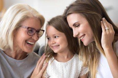 Happy senior grandma embracing kid granddaughter and daughter ha