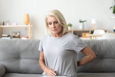 Worried sad older woman touching back feeling back pain