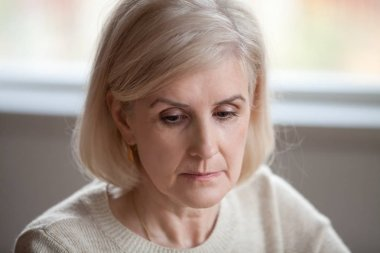 Close up of sad senior woman remembering missing past