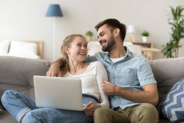 Happy millennial couple spend weekend at home together
