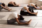 Group of young women practicing yoga, paschimottanasana exercise