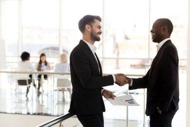 Diverse businessmen shaking hands introducing standing in modern