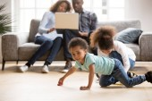 African American married couple using laptop while children play