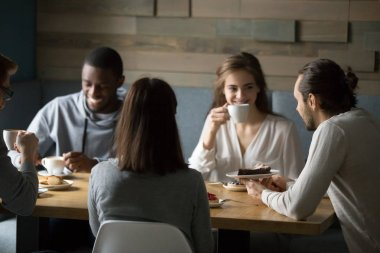 Smiling diverse friends enjoying coffee and desserts in cafe