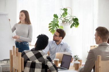 Diverse employees listen to female speaker presenting project