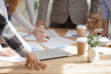 Employees brainstorm with documents on table during meeting