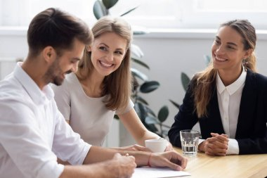 Man signing loan contract sitting at desk with bank workers