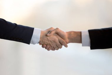 Close up two businessmen in suits shaking hands
