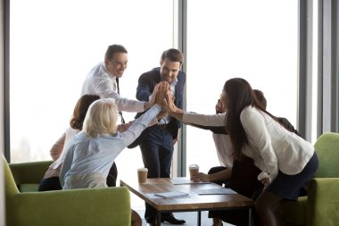 Multi-ethnic businesspeople celebrating success at work giving h