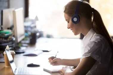 Focused woman wearing headphones write notes study online with t