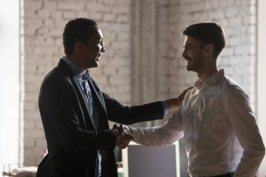 African executive manager handshaking caucasian employee promoti