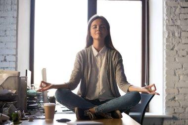 Serene calm business woman sit on office desk meditating