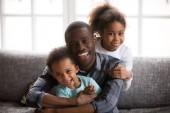 Papà felice africano e i bambini di razza mista a casa