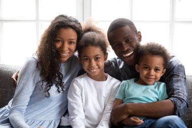 Happy black family of four looking at camera at home
