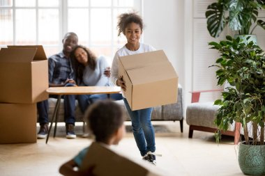 Excited mixed race children holding boxes playing in new home