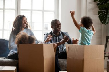 Excited mixed-race kids jumping out of box playing with parents