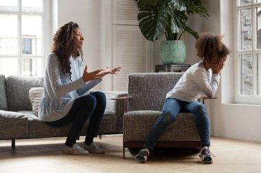 Stubborn african kid ignoring mom scolding, parent and child con