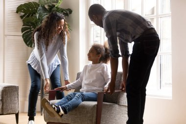Happy african american parents carrying kid daughter on armchair