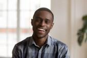 Šťastné veselé africké tisícileté muž při pohledu na fotoaparát doma
