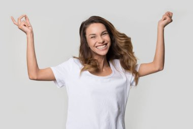 Happy cheerful young woman jumping feeling joy on white background