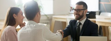 Confident realtor greeting clients young married couple in office