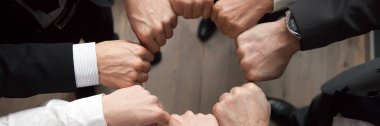 Above horizontal view group businesspeople put fists in circle shape