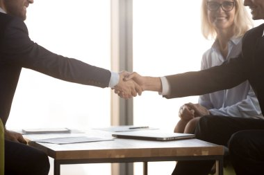 Satisfied business partners in suits shake hands, close up view