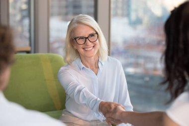Smiling confident mature woman job seeker applicant handshaking hr