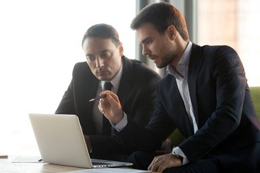 Serious businessmen work together on online project look at laptop